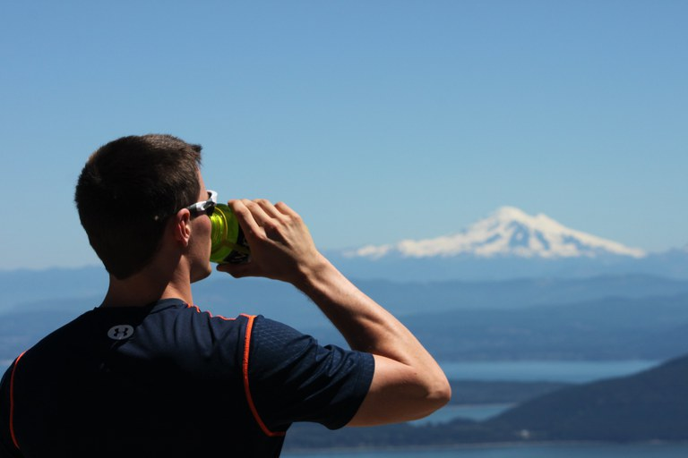 A hiker drinking water with Mount Baker in the background