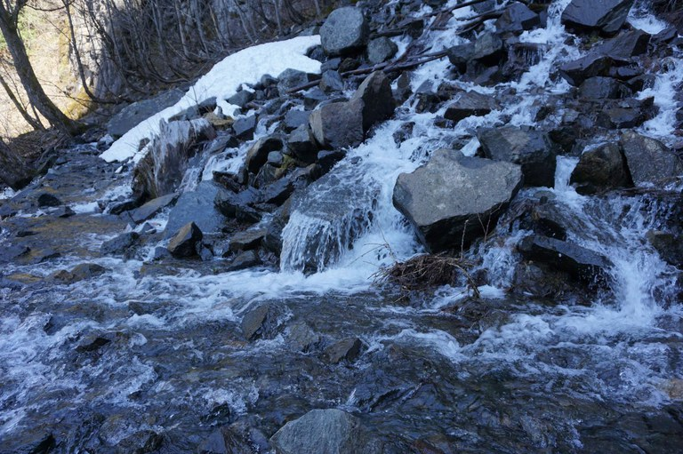 A frozen creek crossing over the trail.