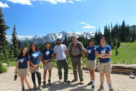 Girls pose with trail bosses, Boston and Alex, after a hard day of building check-steps. Photo by Michelle Piñon