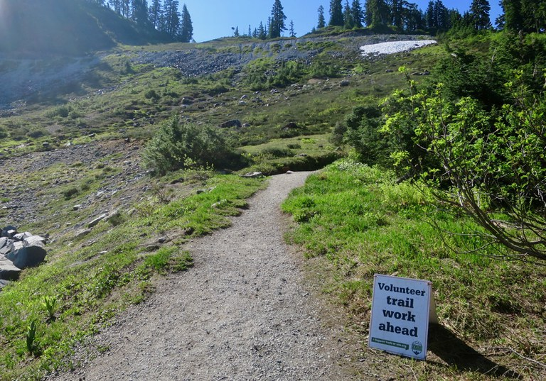 """A sign next to a trail reads """"Volunteer Trail Work Ahead."""""""