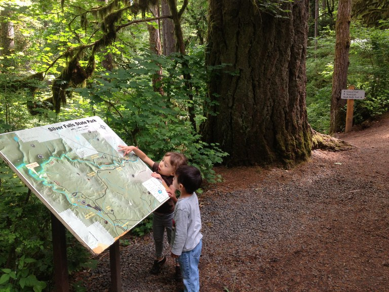 Two small kids touching and looking at an interpretive sign that is much bigger than them.
