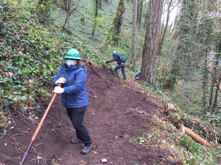Trail work volunteer, wearing a green hard hat and a face mask and holding a rake stands on a section of freshly improved trail.