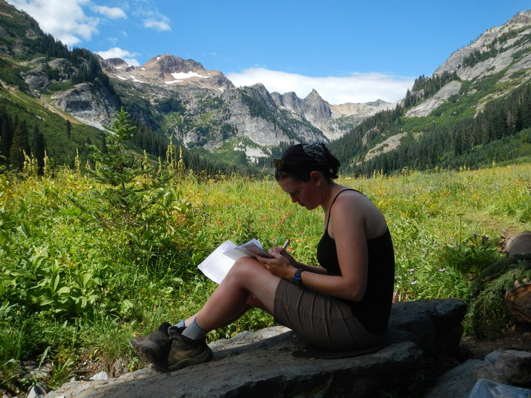 A hiker sits on a rock and writes in a journal.