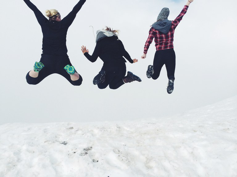 Three hikers jump into the air on a snow-covered mountain. Photo by Veronica Hurm.