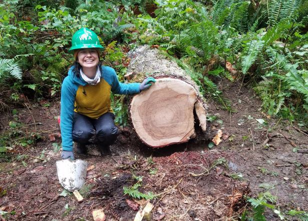 A volunteer smiles next to a newly-cut log. Photo by Robert Canvass