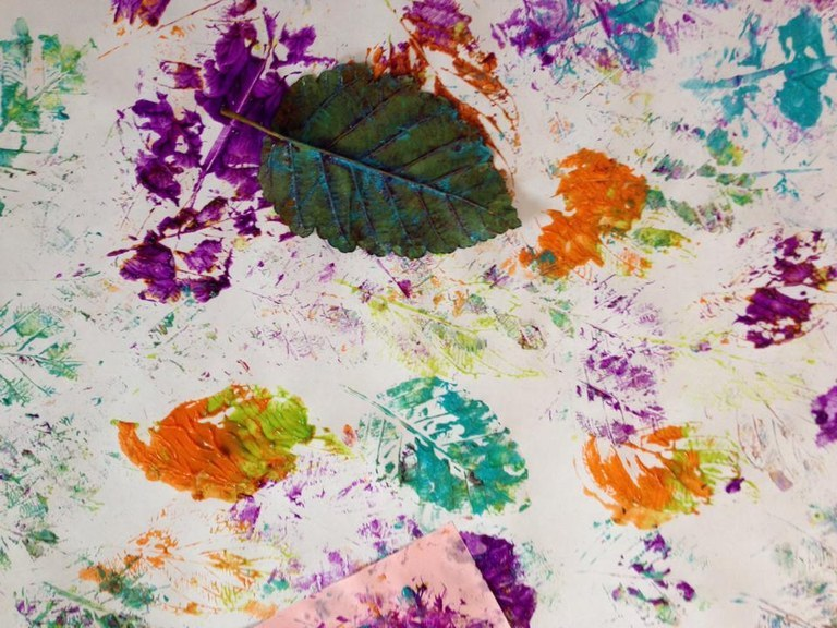 Brightly colored paint prints, made from leaves, cover a white paper.