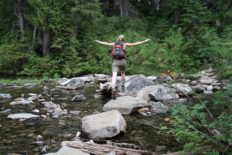 A hiker leaps across stepping stones in a stream.