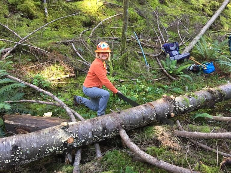 Liz smiles at the camera as she saws through a fallen log.