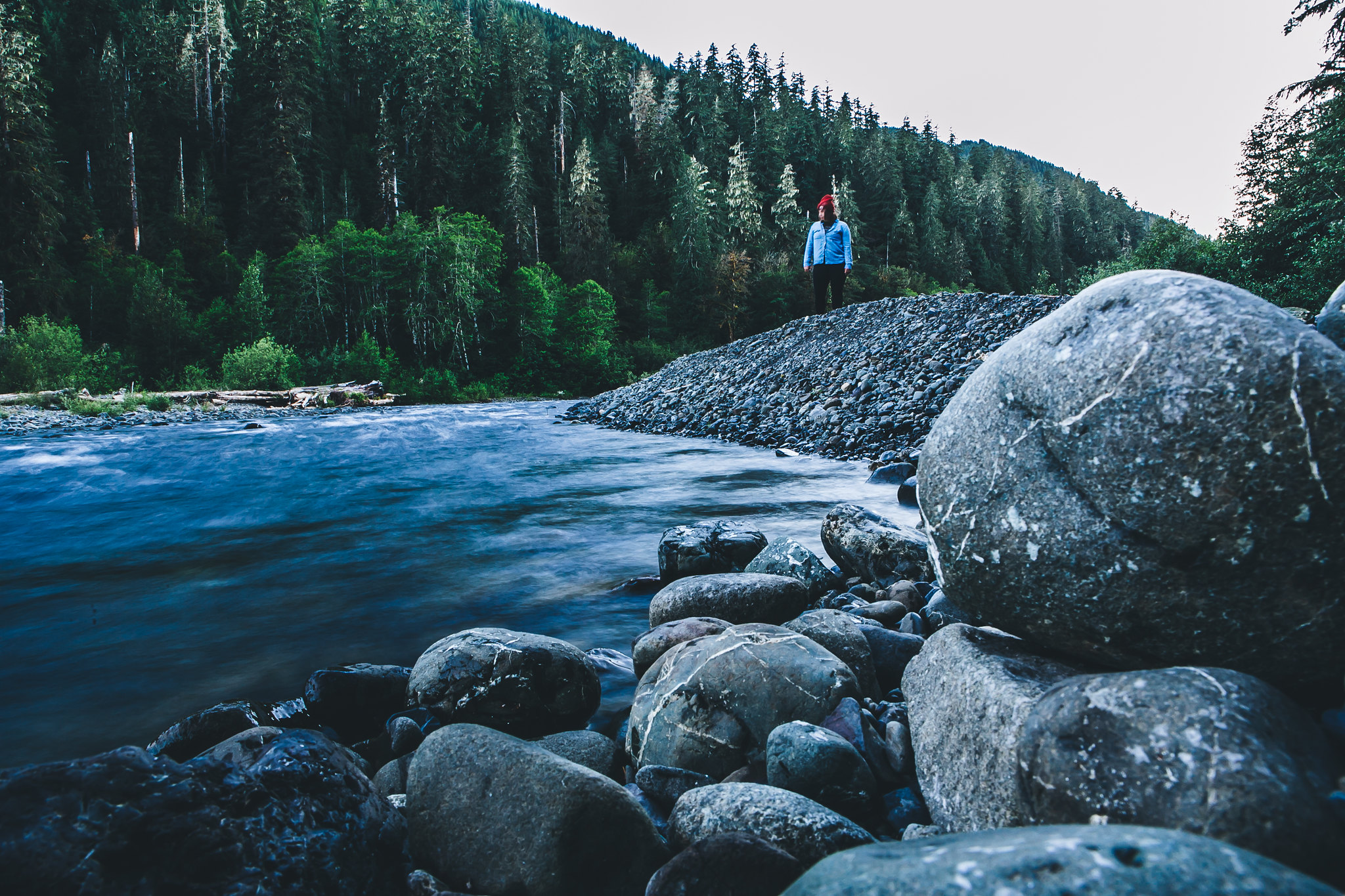 A hiker stands next to the Lower South Fork Skokomish River on a dusk hike in fall. Photo by Rebecca Cooper