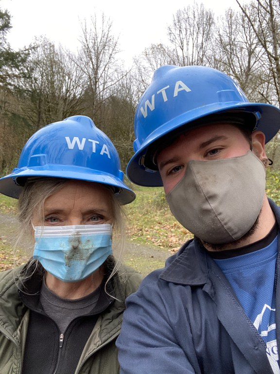 Two crew leaders, wearing blue WTA hard hats and face masks, pose for a selfie.