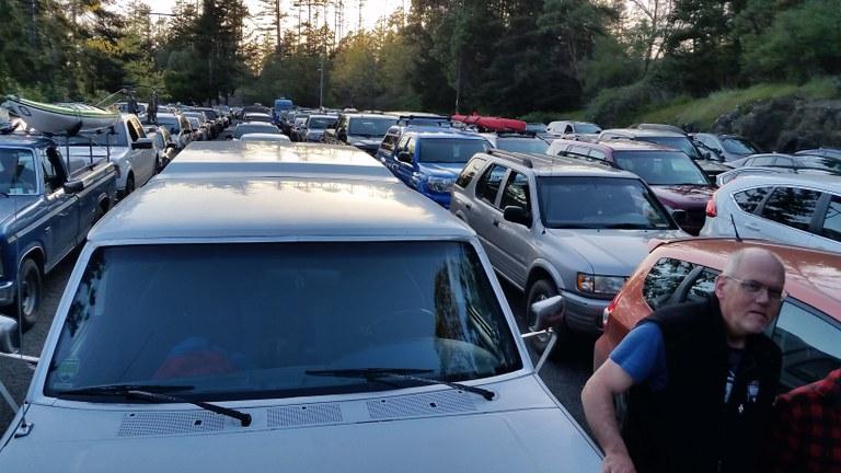 A man walks through a crowded parking lot at the trailhead. Photo by Barbara B.