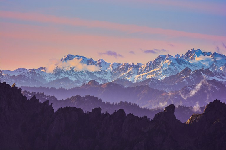 Layers of mountains, with snowy peaks in the background and a purple sunset.