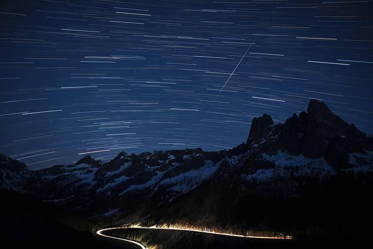 A starry sky and mountains with an illuminated highway curving around the base of the mountains.