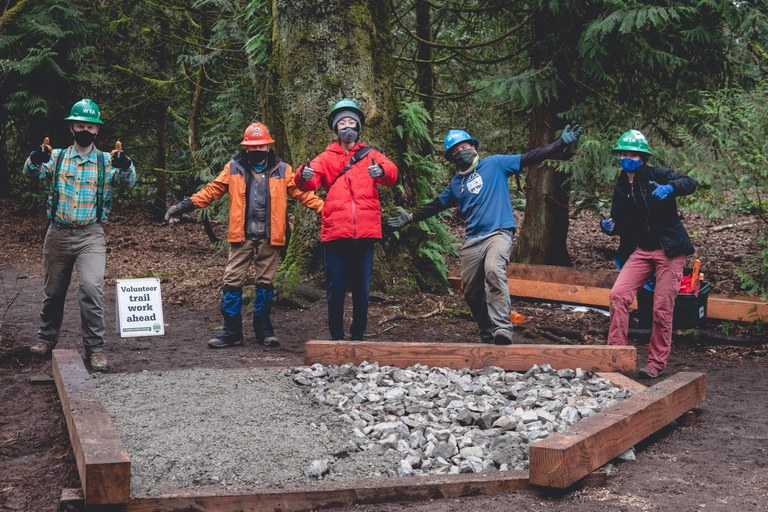 A group of volunteers pose for a photo on trail. All are wearing masks and hard hats.