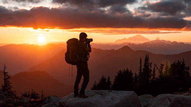 A photographer takes a picture of a mountain sunset.