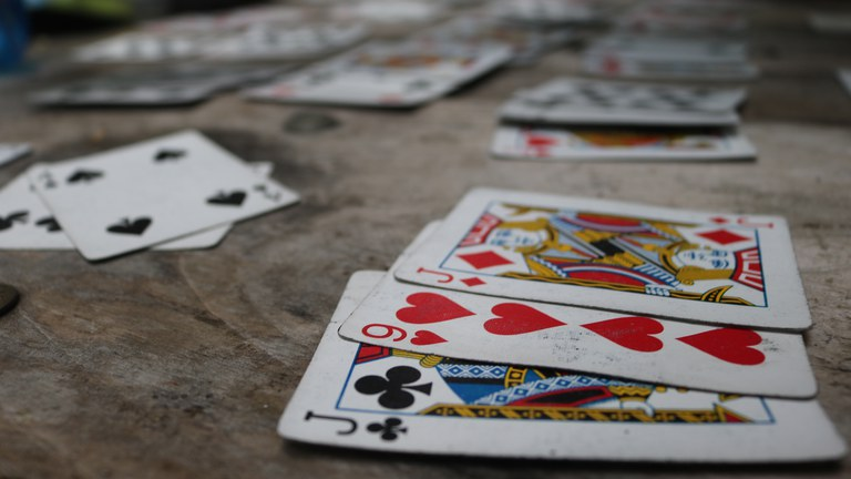 Playing cards spread out on a wooden picnic table.
