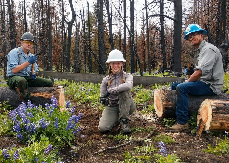 Three trail crew members pose for a photo on trail. The one in the center is wearing a white hat, the other two have green hats.