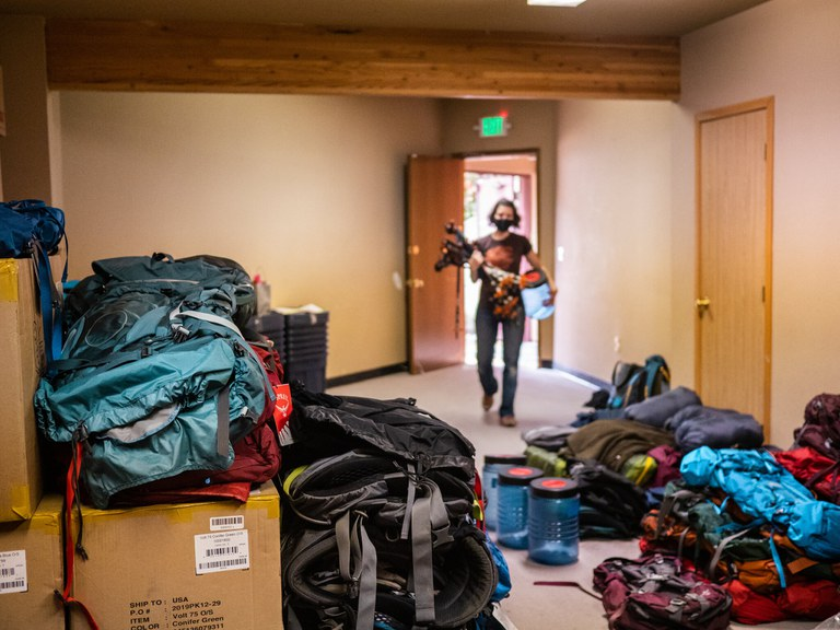 A woman carrying a load of trekking poles and a bear canister walks into a room full of outdoor gear and boxes.