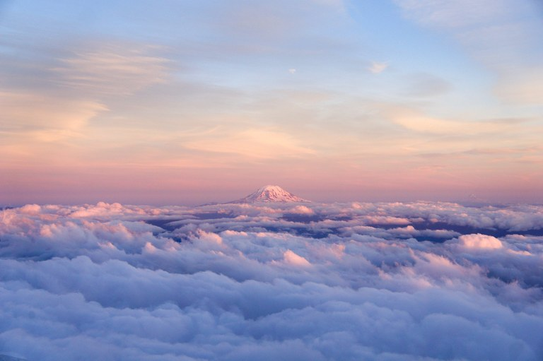 Mount Rainier rising above the clouds with pink and blue sky in the background.