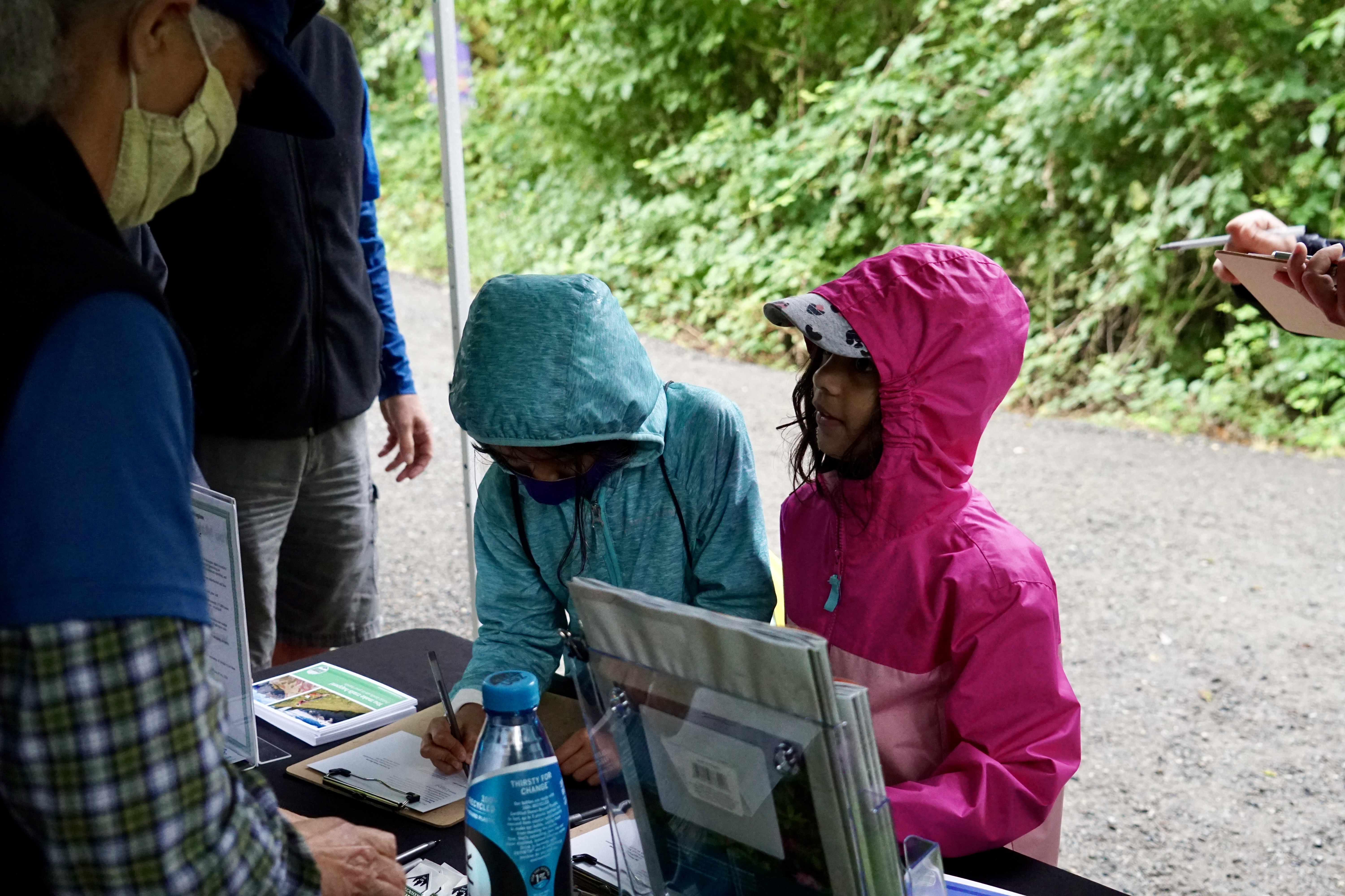Two young children wearing rain jackets sign postcards in support of trails.