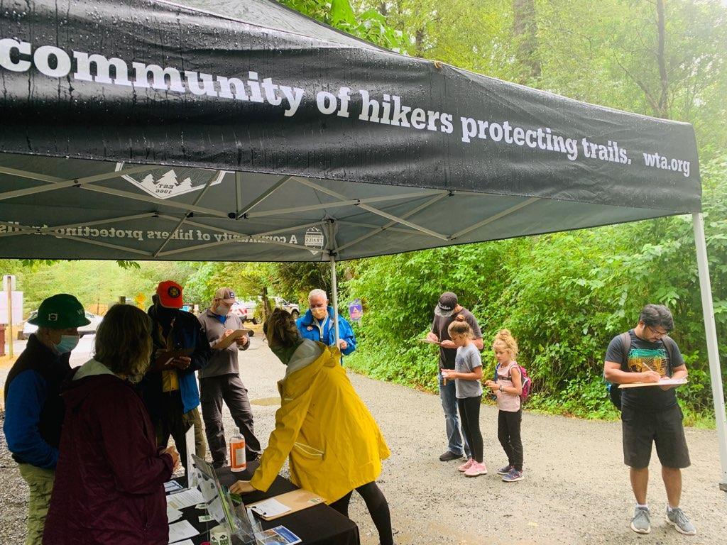 Hikers in rain jackets sign postcards below a wet Washington Trails Association tent.