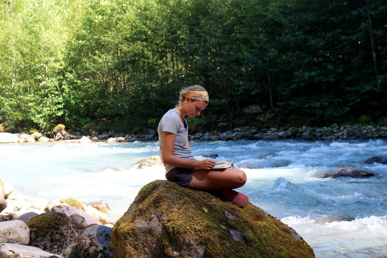 A woman sits on a rock next to a river and reads a book. Photo by McKenzie Carlson.