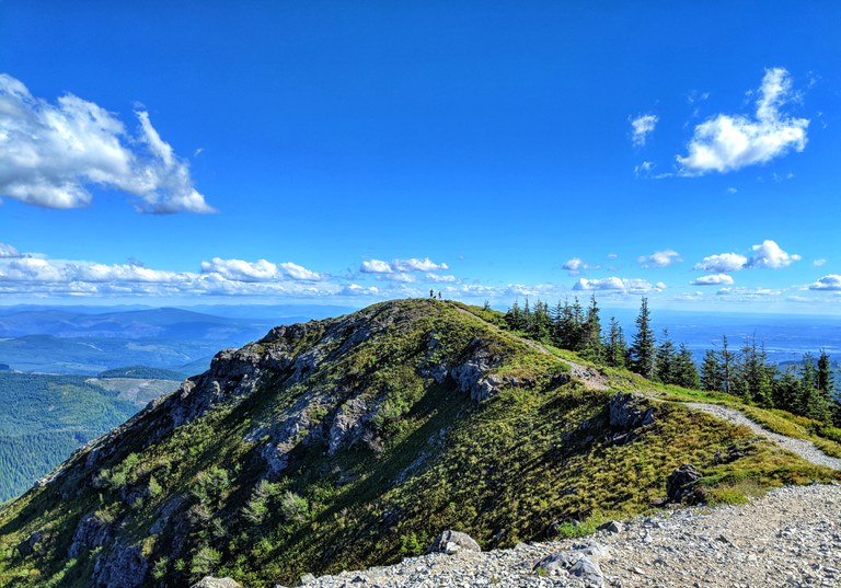 A trail leads to a mountain summit with overlooking a forested valley far below.