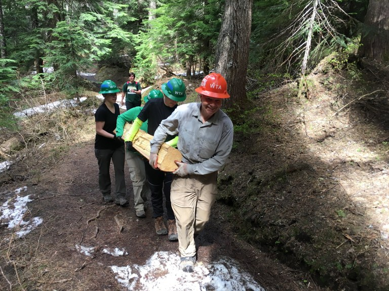 A group of volunteers carries a log across a trail with some snow on it. Photo by Hannah Tennent.