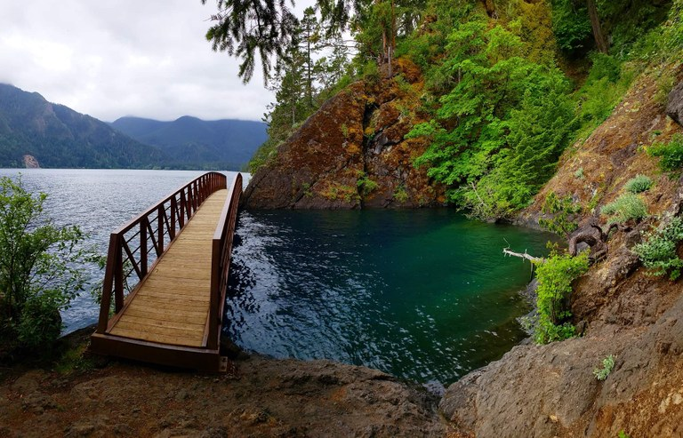 A bridge crosses over an aquamarine inlet on the shore of Lake Crescent. Photo by Marissa Edwards.
