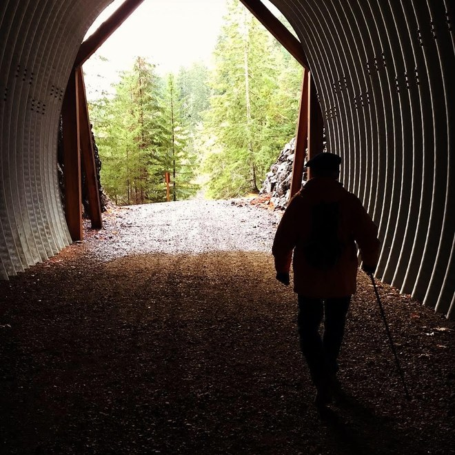 A hiker walking into the light at the end of an old railroad tunnel. Photo by maryvr.