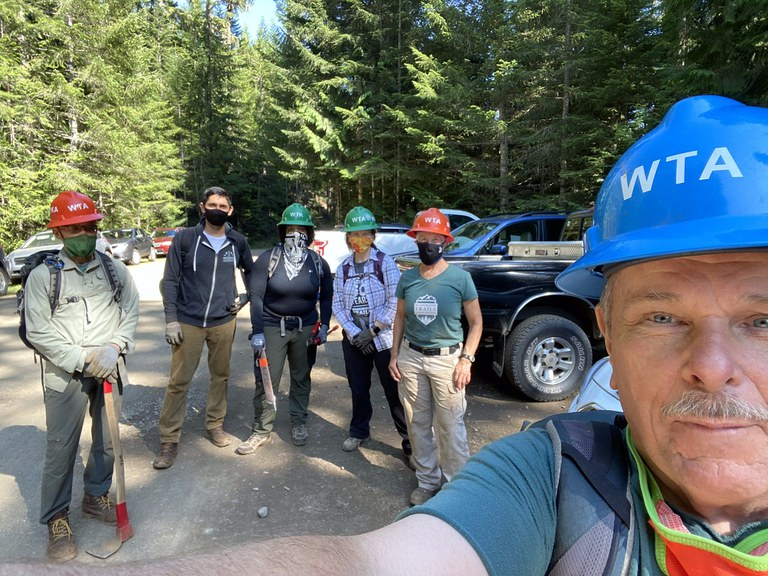 Crew Leader Patrick Sullivan snaps a selfie with his masked-up crew in the background before heading out on a multi-day trip to Marmot Pass. Photo by Patrick Sullivan