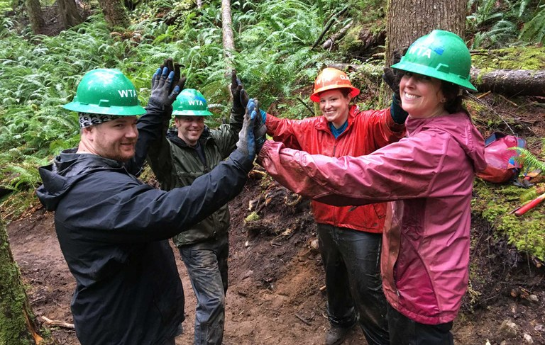 Four WTA volunteers celebrate a job well donw with a group high five