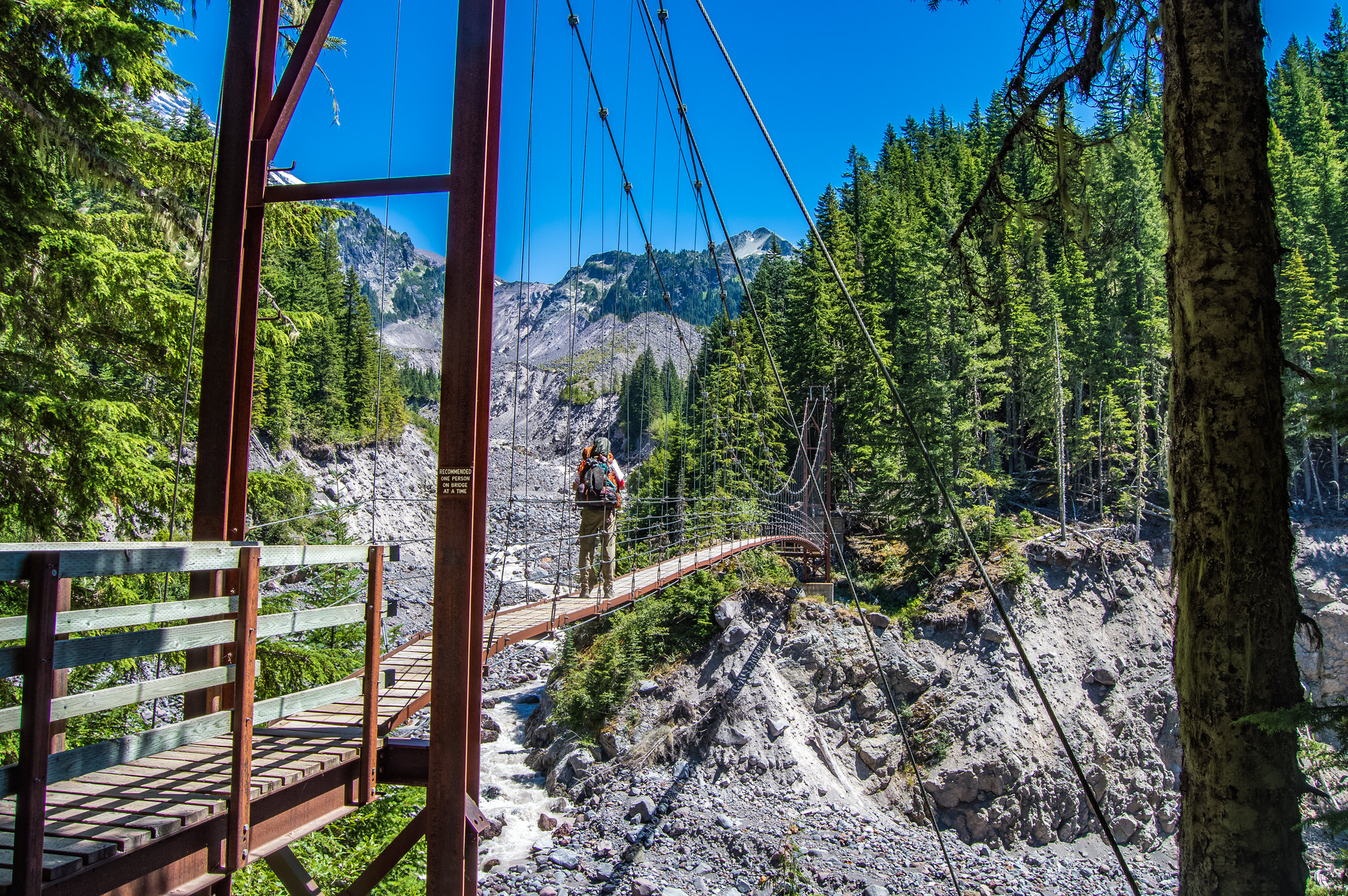 Wonderland Trail adventurer crossing the Tahoma Creek Suspension Bridge - Austin Miller