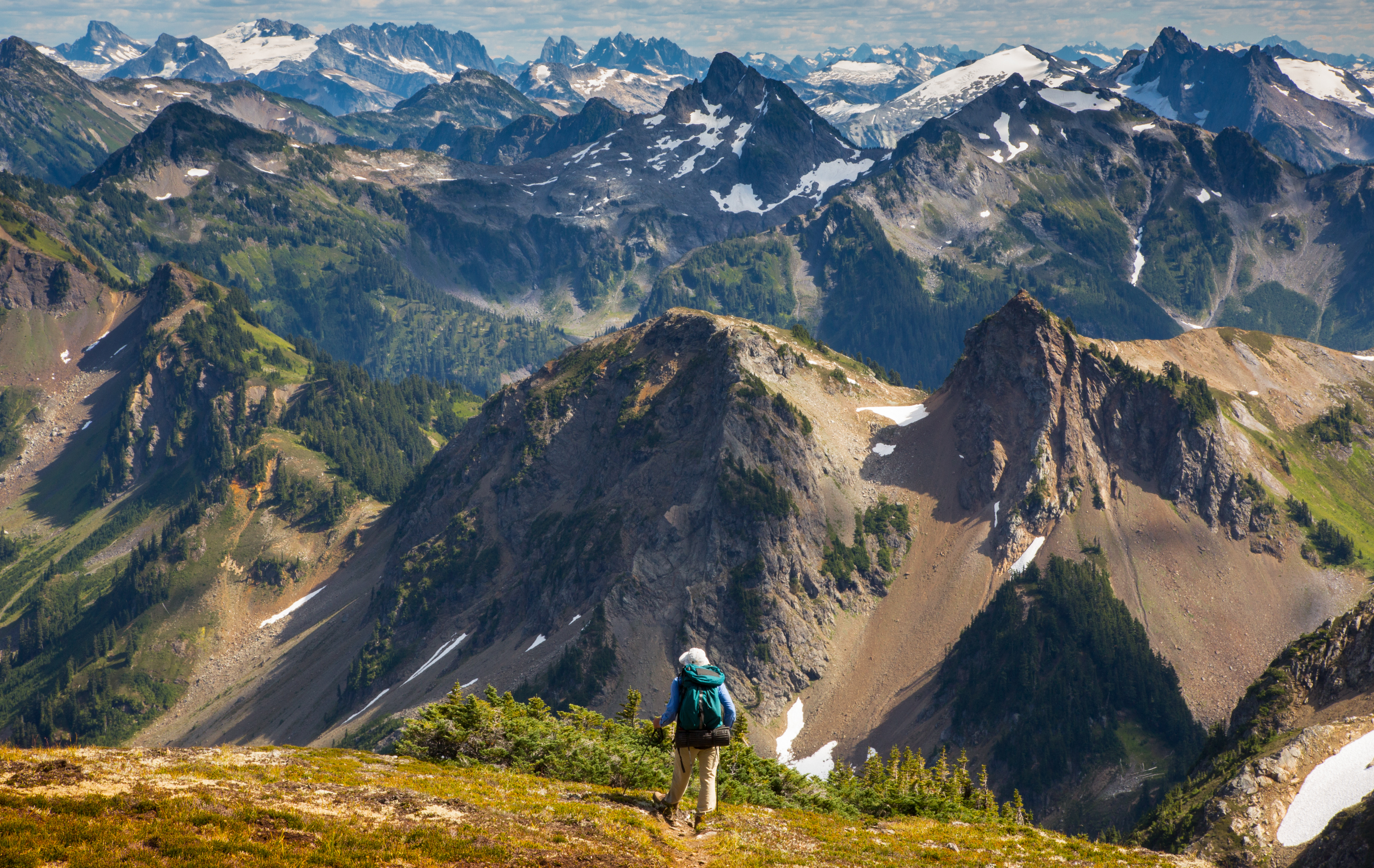 Image displays a hiker looking off at the mountain line, where there are layers of mountain peaks in front of him.
