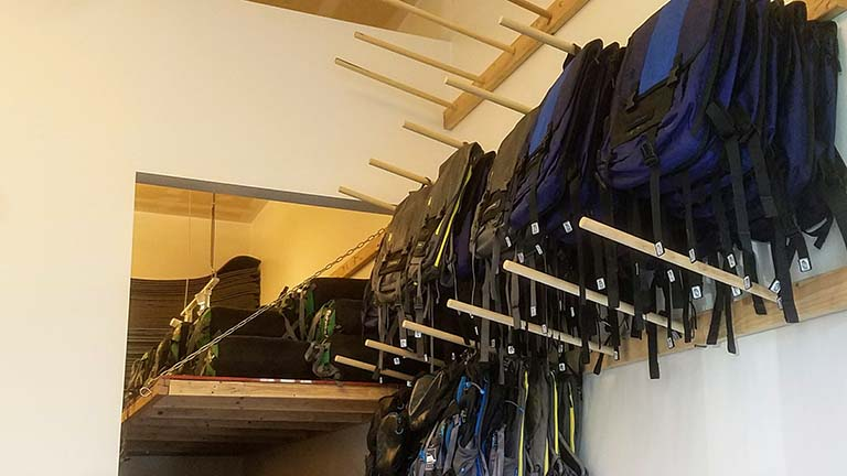 Dowels at the Gear Library with backpacks and trekking poles