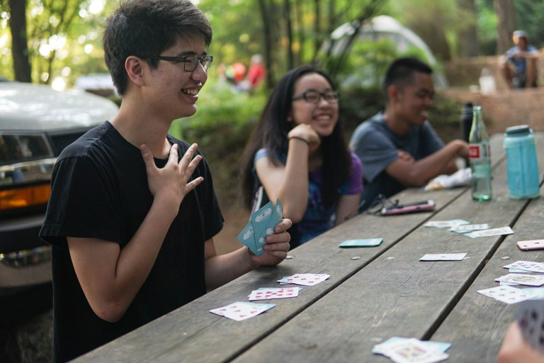 3 smiling teens enjoy a game of cards in camp on their Youth Volunteer Vacation at Moran State Park. Photo by Britt Lê