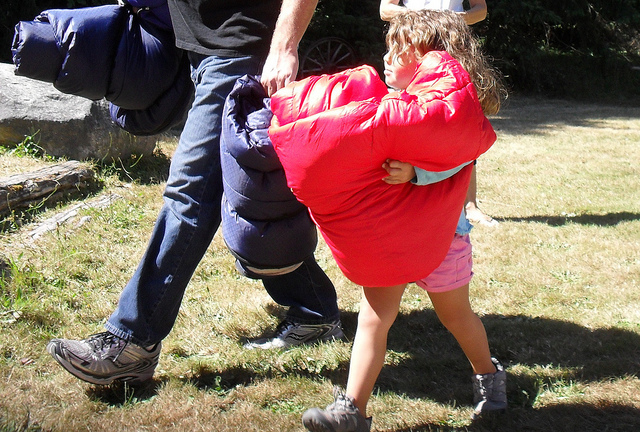 Girl helps carry camping gear