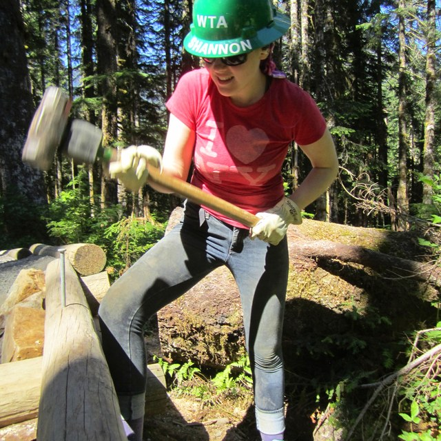 A youth volunteer pounds in a stabilizing rod along the Big Four Ice Caves trail. Photo by Kay Sadowitz.